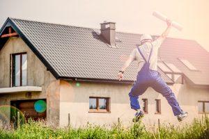 家とジャンプする男性